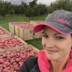 Debra Turner smiling by apple box